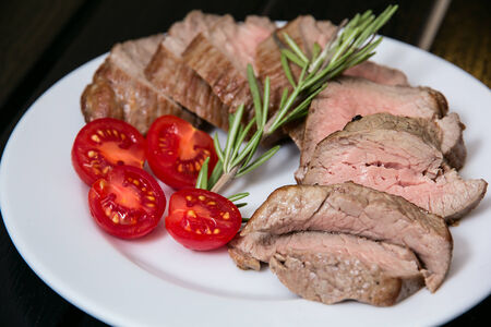Juicy steak on the plate with some tomatoes Stock Photo