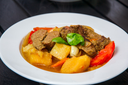 Ragout with meat and vegatables on the white plate Stock Photo