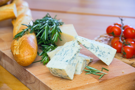 Cheese, bread and rosemary on the wooden board Stock Photo
