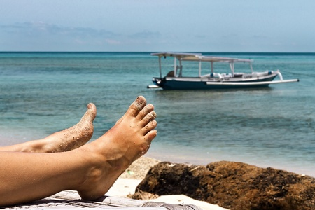 Feet on the background of the ocean, the boat and the mountains Stock Photo - 19027340