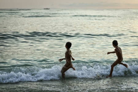 Kids playing with the waves in the ocean at yellow sunset photo