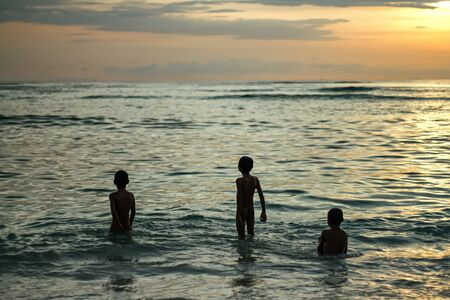 Kids playing with the waves in the ocean at yellow sunset Stock Photo - 19027951