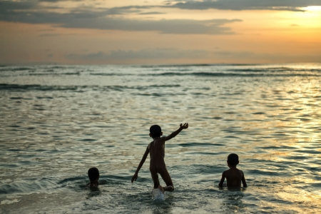 Kids playing with the waves in the ocean at yellow sunset Stock Photo - 19027942