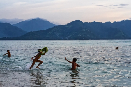 Kids playing with the waves in the ocean at yellow sunset Stock Photo - 19027956