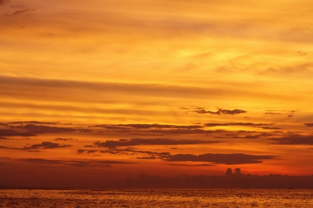 Yellow and red sunset over a calm ocean photo