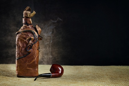 Brown leather vintage bottle with a pipe on a dark background photo
