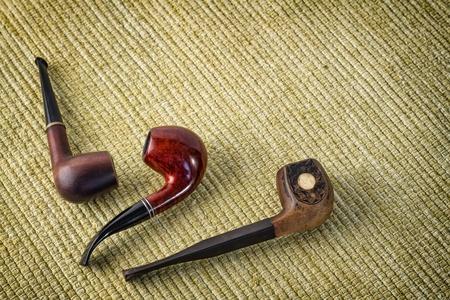 Three vintage smoking pipe on the yellow burlap Stock Photo - 19409020