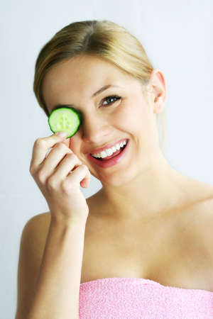a young, beautiful, happy woman is holding some cucumber in front of her smiling face Stock Photo - 1455758