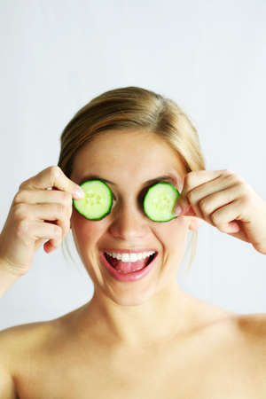 a young, beautiful, happy woman is holding some cucumber in front of her smiling face Stock Photo - 1455757