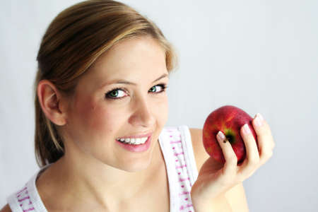 a healthy, beautiful, happy woman is holding an red apple in front of her smiling face Stock Photo - 1455764