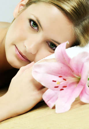 a young beautiful woman is relaxing in spa - wellness with a flower lily Stock Photo