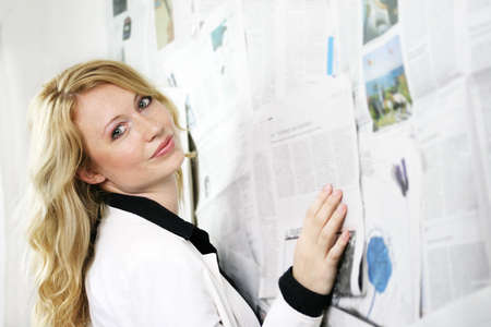 a young businesswoman against a wall with a lot of newspapers Stock Photo - 1455766