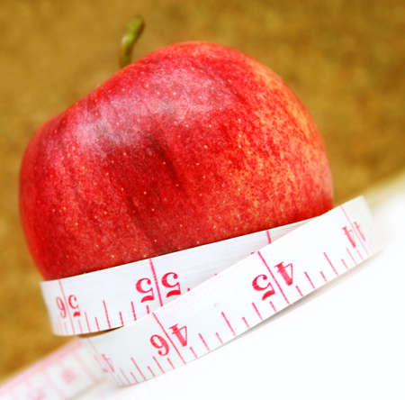 Measurement tape wrapped around red apple - health, diet photo
