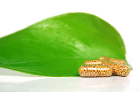 Some yellow pills on a green leaf - homeopathy