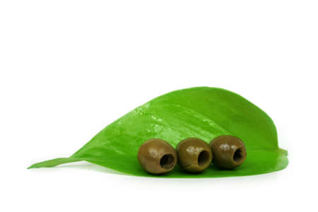 good cholesterol: A few olives on a green leaf against white background