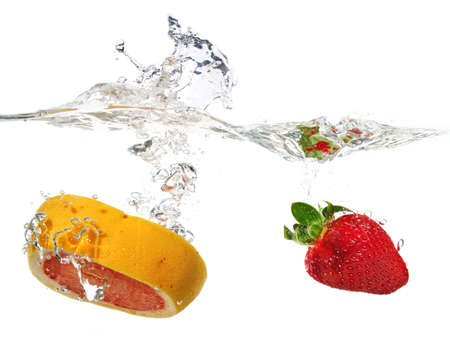 a grapefruit and a strawberry are falling in water with a big splash photo
