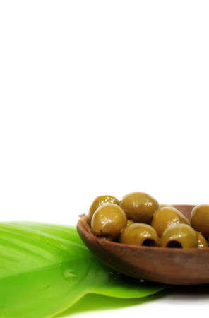 good cholesterol: A few olives in a bowl of lumber on a green leaf