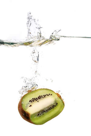 a kiwi fruit is falling in water with a big splash and a lot of water drops photo