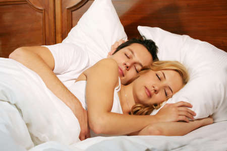 a attractive young couple is sleeping in there bed at home