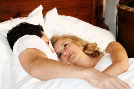 appartment: a attractive young couple is smiling in there bed at home