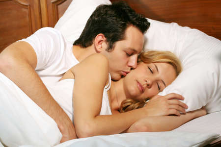a attractive young couple is kissing in there bed at home