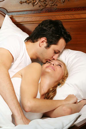 a attractive young couple is kissing in their bed at home photo