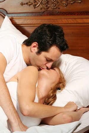 besos apasionados: una atractiva joven pareja se besa a su cama en su casa