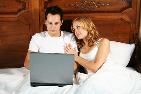 a young man is working with his notebook in bed, while his girlfriend is angry because of it photo