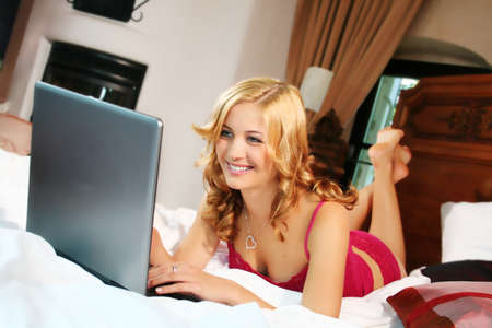 a young beautiful woman is working with her notebook in her bed at home Stock Photo