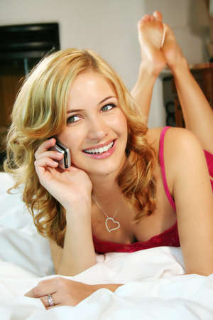 a young smiling beautiful woman is calling with her mobilephone in her bed at home photo