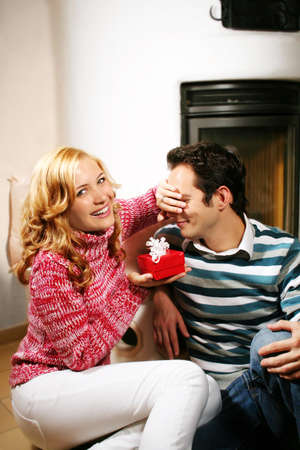 a young attractive couple in christmas time - she is holding a gift