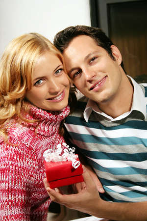 a young attractive couple in christmas time - he is holding a gift