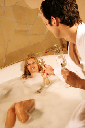 A young beautiful couple is taking a bath with champagne in a glass