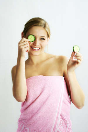 a young, beautiful, happy woman is holding some cucumber in front of her smiling face Stock Photo
