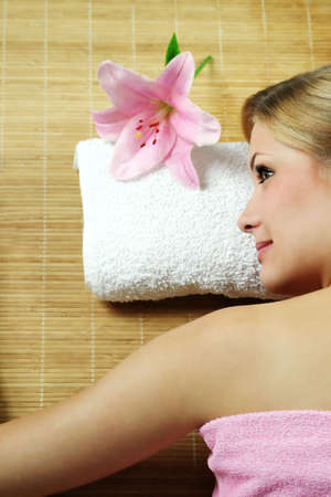 a young beautiful woman is relaxing in spa - wellness with a flower lily Stock Photo - 1771538