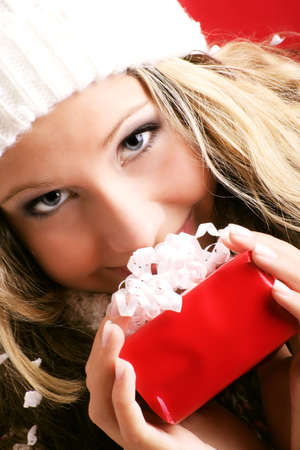 winter portrait of a beautiful young smiling woman with a gift in her hands photo