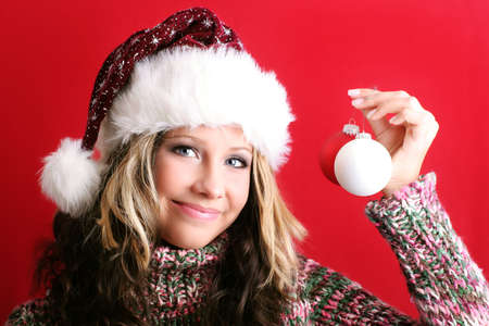 winter portrait of a beautiful young smiling woman with some christmas tree balls