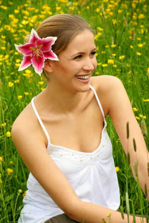 happy woman with a flower in her hair on a meadow Stock Photo - 5003275