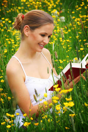 happy woman is sitting on a meadow and is reading a book Stock Photo - 5003273
