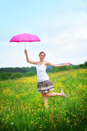 woman on a meadow in front of blue sky with an pink umbrella photo