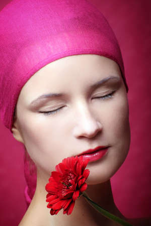 beauty portrait of a young woman in pink with a gerbera flower