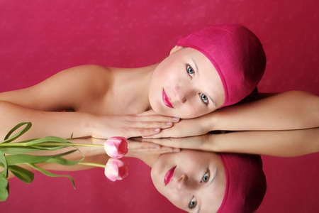 beauty portrait of a young woman in pink with a tulip flower on a mirror Stock Photo