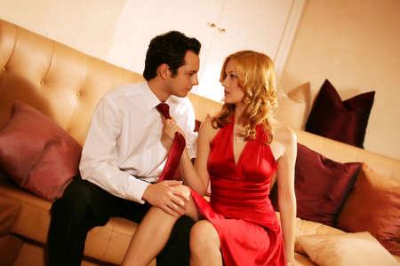 fashionable couple: joven y rico joven est� sentado en una sala de estar y tener un argumentan