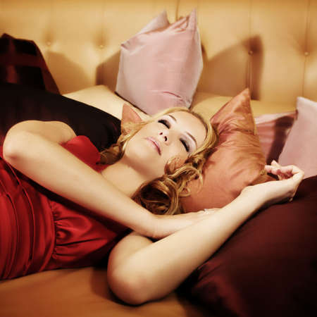 a young, beautiful woman with a red dress is sleeping on a lounge photo
