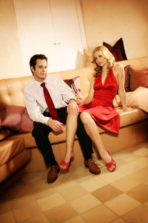 lounging: a attractive, young and rich couple is sitting on a lounge