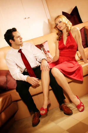a attractive, young and rich couple is sitting on a lounge photo