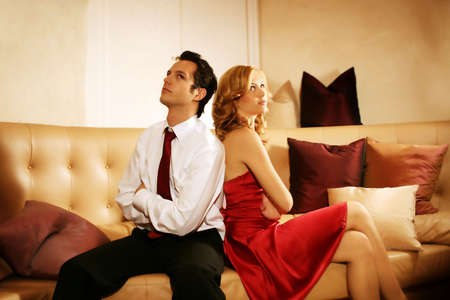 married couples: young and rich couple is sitting on a lounge and have an argue