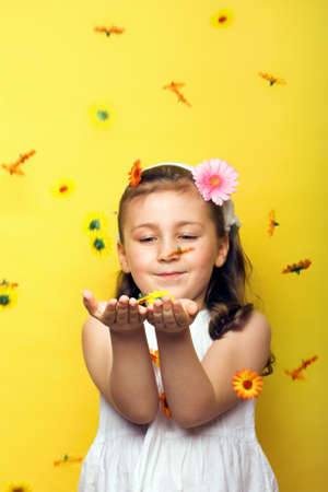 smiling beautiful young girl with falling flowers at spring photo
