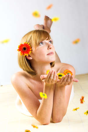 young beautiful woman with a towel and falling flowers photo