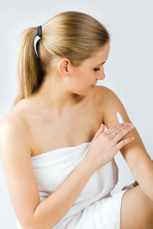 a young beautiful woman is applying some creme on her skin Stock Photo